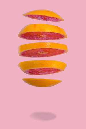 Floating levitating ripe grapefruit on pink background. Vitamins, healthy diet concept. Minimal fruit idea. Sliced grapefruit floating in the air. Creative concept with flying fruits. Stock Photo