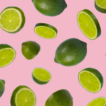 Falling limes isolated on a pastel pink background. Minimal fruit concept.Vitamins, healthy diet concept. Sliced lime floating in the air. Creative concept with flying fruits.