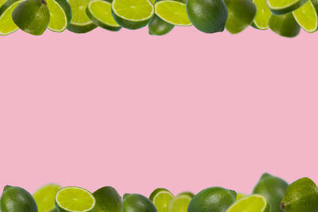 Frame of sliced fresh limes isolated on pastel pink background. Vitamins, healthy diet and detox concept. Minimal creative concept  fruit concept with free space for text.
