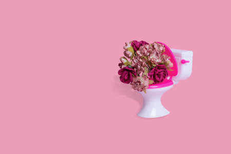 Creative funny idea made of toilet bowl with many colorful flowers on a pink background. Minimal humorous concept of surprises and gifts. Free space for text - copy. Stock Photo