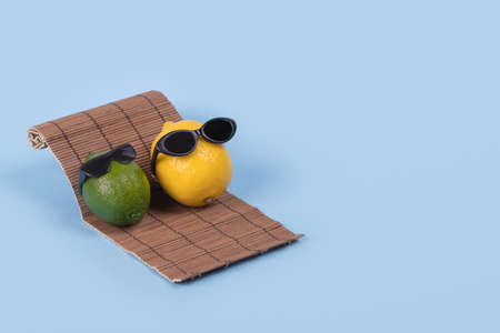 Creative fun idea with a lemon and lime in sunglasses lying on a sun bed on a blue background. Minimal travel and vacation concept, summer stylish tropical fruit. Summertime color mood. Fashion, holiday, party and summer trend. Copy space.