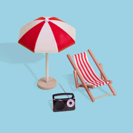 Creative minimal summer idea made of  sun umbrella, deck chair and radio on a pastel blue background. Modern concept of vacation, travel, fun and summer time.