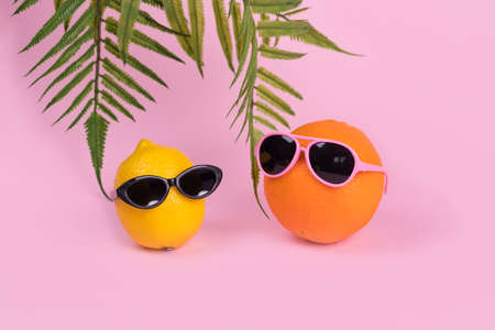 Creative idea with orange and lemon fruit hipster in sunglasses on pastel pink background. Minimal travel concept, summer stylish tropical fruit. Art fashionable vacation concept. Summertime color mood.Fashion and trend. Stock Photo