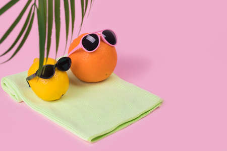 Orange and lemon fruit hipster in sunglasses lying on a towel on a pastel pink background. Minimal travel concept, summer stylish tropical fruit. Creative art fashionable vacation concept. Summertime color mood.Fashion and trend.