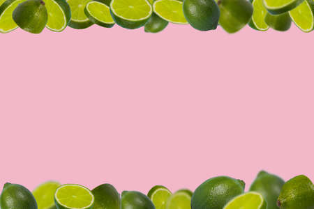 Trendy frame of sliced fresh limes isolated on pastel pink background. Vitamins, healthy diet and detox concept. Minimal creative concept  fruit concept with free space for text.