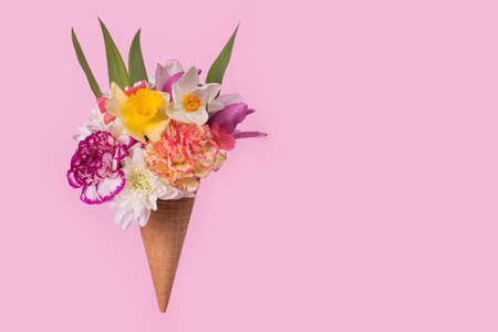 Ice cream cone with colorful flowers and leaves on a pastel pink background. Minimal spring or summer concept. A modern fun concept of gifts, anniversary and love. Copy space Stock Photo