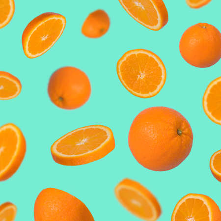 Minimal idea with fresh orange sliced on trendy green background. Minimal fruit concept.Vitamins, healthy diet concept. Sliced and whole orange floating in the air. Creative concept with flying fruits.