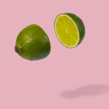 Minimal idea with fresh lime sliced on pastel pink background. Minimal fruit concept.Vitamins, healthy diet concept. Sliced lime floating in the air. Creative concept with flying fruits.