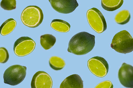 Falling limes isolated on a pastel blue background. Minimal fruit concept.Vitamins, healthy diet concept. Sliced lime floating in the air. Creative concept with flying fruits. Stock Photo
