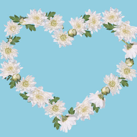 Heart shape made with white flowers and leaves arrangement on pastel blue background. Creative Minimal  concept of Valentines, Women's, Wedding Day.Romantic floral visual trend. Copy space