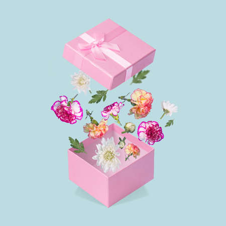 Luxurious Gift box with flying coloful flowers and leaves on a pastel blue background. Minimal spring or summer concept. A modern fun concept of gifts, wedding, anniversary and love. Stock Photo