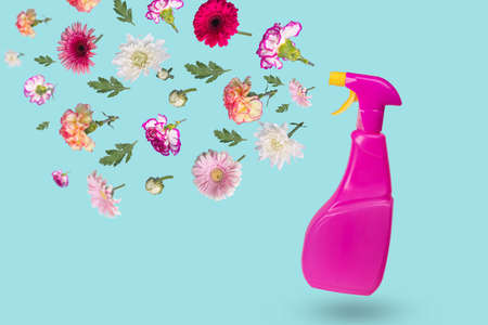 Creative minimal idea made from a bottle with a spray and various flowers flying in the air. The concept of protection, spring cleaning, disinfection and refreshment. Copy space Stock Photo