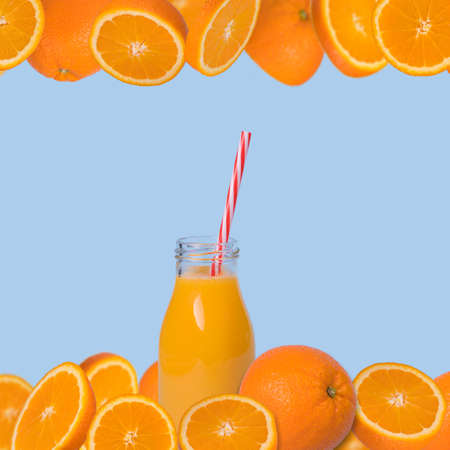 Minimal creative idea, frame made of fresh slices of orange and  bottle of juice with straw on a light blue background. Vitamins, healthy diet trendy concept with many fruits. Stock Photo