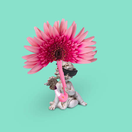 Minimal creative idea with a happy angel in sunglasses with sun umbrella of flower and flamingo on a trendy green background. Funny art design. Standard-Bild