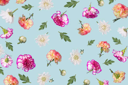 Spring or summer pattern made with different colorful flying flowers and leaves on light blue background, trendy floral layout. Creative Minimal concept of nature, Birthday, Mother's, Valentines, Women's, Wedding Day.