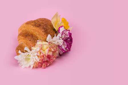 Croissant with many different colorful flowers on a pastel pink background. Minimal spring or summer concept. A modern fun concept of stylish food, gifts, anniversary and love. Copy space