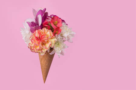 Ice cream cone with many different colorful flowers on a pastel pink background. Minimal spring or summer concept. A modern fun concept of gifts, anniversary and love. Copy space