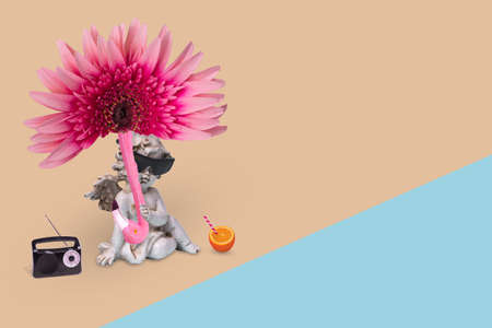 Creative minimal idea with a happy angel in sunglasses with sun umbrella of flower and flamingo, enjoying on the beach. Funny pop art design. Creative concept of holiday, travel and enjoyment.