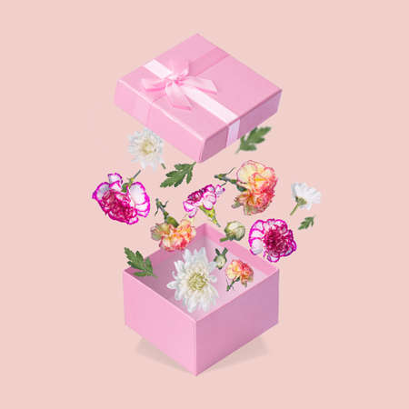 Luxurious Gift box with flying coloful flowers and leaves on a light pink background. Minimal spring or summer concept. A modern fun concept of gifts, wedding, anniversary and love. Standard-Bild