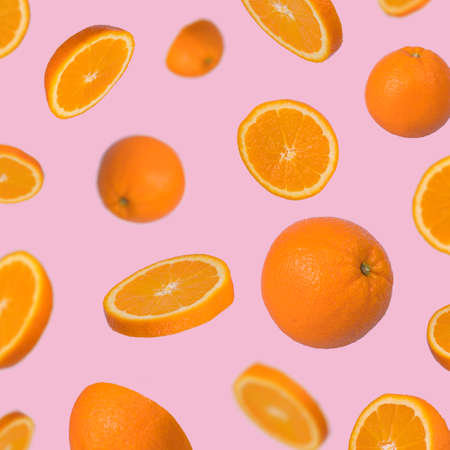 Minimal idea with fresh orange sliced on pastel pink background. Minimal fruit concept.Vitamins, healthy diet concept. Sliced and whole orange floating in the air. Creative concept with flying fruits. Standard-Bild
