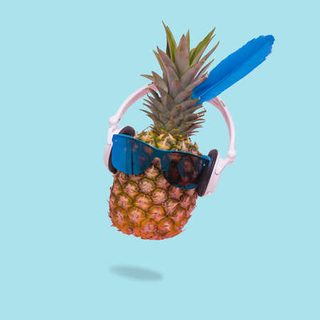 Creative trendy summer poster with pineapple wearing sunglasses and headphones on pastel blue background . Minimal scene of fun, party, fashion, trend and funny art design.