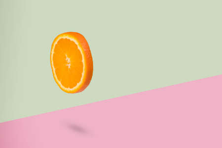 Minimal creative  idea with fresh flying orange piece on a light green and pink background. Vitamins, healthy diet, cosmetic and beauty concept. Sliced orange floating in the air. Creative concept with flying fruits.