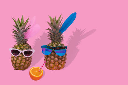 Female and male pineapple hipster in sunglasses, stylish fruit couple. Minimal concept, summer tropical pineapples. Creative art fashionable vacation concept. Summertime color mood, pineapple.Fashion and trend.