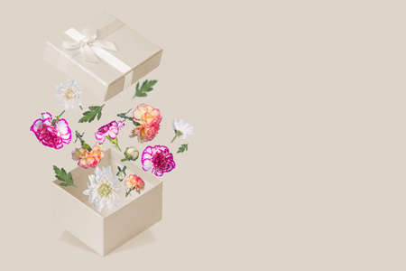 Luxurious Gift box with flying colorful flowers and leaves on a trendy colored background. Minimal spring or summer concept. A modern fun concept of gifts, wedding, anniversary and love. Free space for text. Standard-Bild