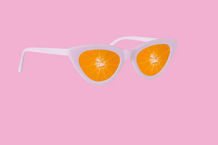 Trendy summer idea made of sunglasses and fresh slices of orange fruit. Creative minimal concept of vacation, travel, beach and relax. Artwork design  with copy space for marketing and advertising. Standard-Bild