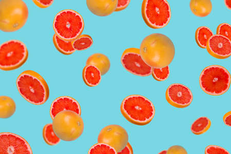 Minimal idea with fresh grapefruit sliced on trendy blue background. Minimal fruit concept.Vitamins, healthy diet concept. Sliced and whole grapefruit floating in the air. Creative concept with flying fruits.