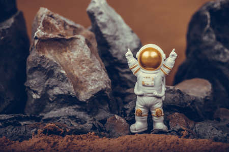 Astronaut raising arms while standing on rocky mountain. Spaceman wearing white space suit and helmet. Concept of cosmonautics, space travel, freedom and winning.