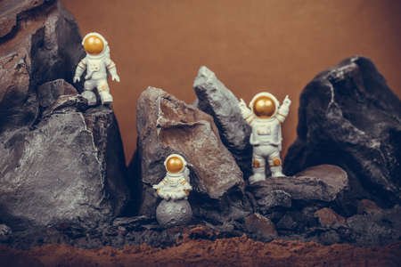 Astronaut with gold visor and White Spacesuit on rock surface with space background. One astronaut on the moon sitting and meditating while another astronauts celebrating success.