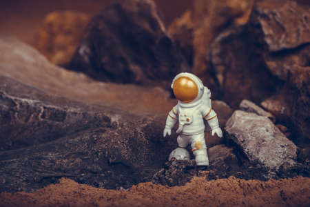 Astronaut with gold visor and white Spacesuit on rock surface with space background. Standard-Bild
