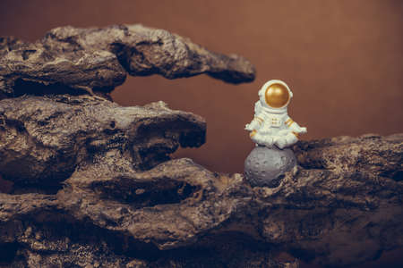 Astronaut wearing white space suit and helmet and meditating while sitting on the moon. Concept of cosmonautics, space travel, freedom, relaxing and peace of mind. Standard-Bild
