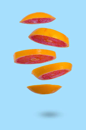 Floating levitating ripe grapefruit on a blue background. Vitamins, healthy diet concept. Minimal fruit idea. Sliced grapefruit floating in the air. Creative concept with flying fruits.