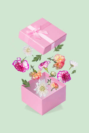 Gift box with flying coloful flowers and leaves on a pastel green background. Minimal spring or summer concept. A modern fun concept of gifts, wedding, anniversary and love.