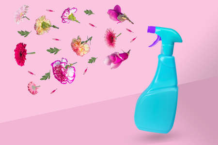 Creative minimal idea made from a blue bottle with a spray and various flowers flying in the air. The concept of protection, spring cleaning, disinfection and refreshment. Artwork design  with copy space for marketing and advertising.