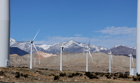 turbin: White Wind Turbines in a row with a snow capped mountains and blue sky in the background.  Stock Photo