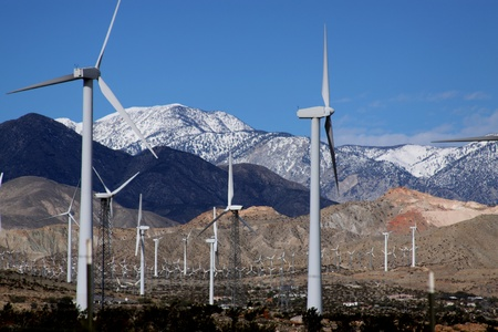 turbin: White Wind Turbines in a row with a snow capped mountains and blue sky in the background.  Photo taken southern California.