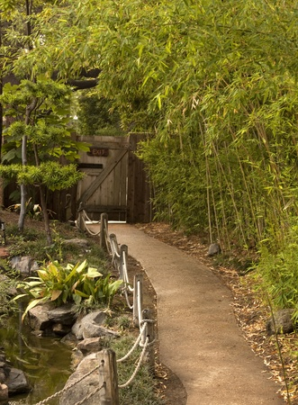 Pathway to Exit gate in a garden of green trees and flowers and a stream of water  Imagens