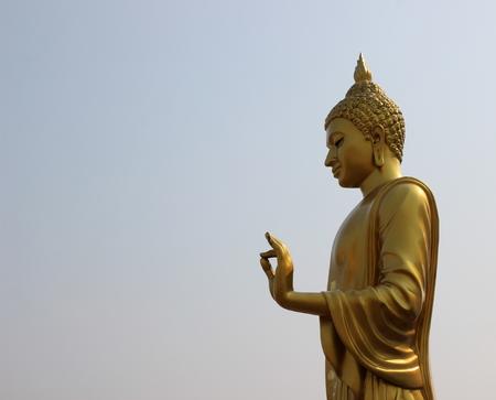dhamma: golden buddha statue on sky background