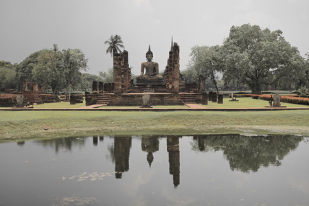dhamma: buddhist statue in old structure of church on water reflect