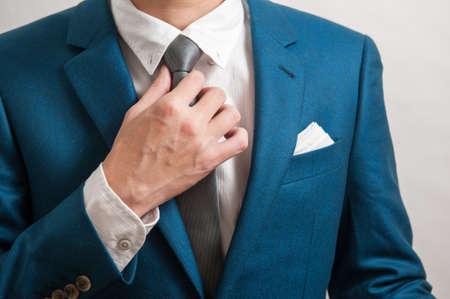 man in suit adjusting necktie Imagens