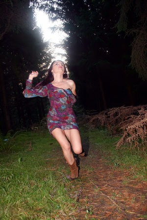 Scared woman in the forest runs and seeks salvation photo