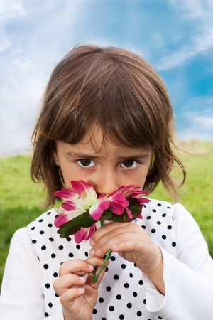 Happy little girl smelling flowers in his hand against the blue sky photo