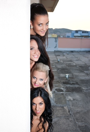 appearing: Four smiling women appearing behind the wall