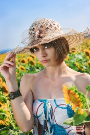 Young pretty woman on a sunflowers background photo