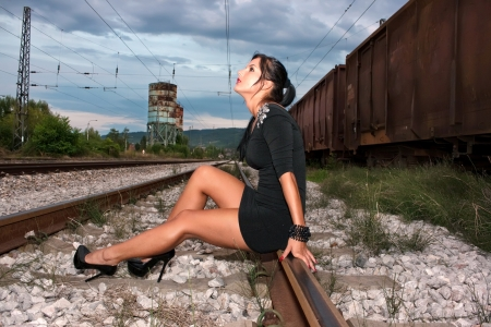 Beautiful young woman in a black dress on a railway line photo