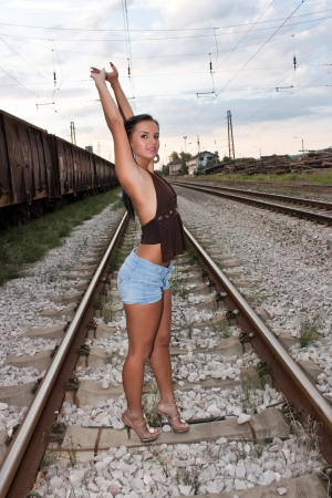 Beautiful young woman in shorts standing on a railway line photo