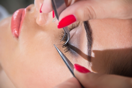 tweezers: Beautiful young woman eyelash extension